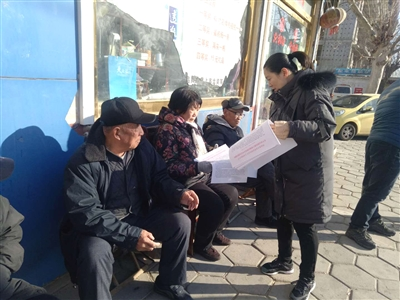 社区工作人员向市民发放宣传单并讲解相关知识