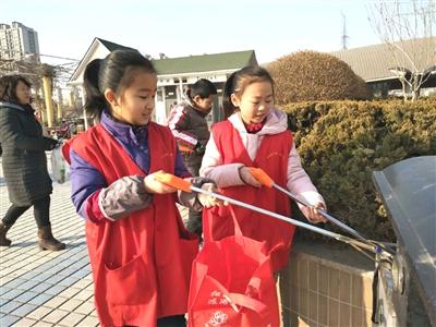 两名小学生在五星人民广场捡拾垃圾