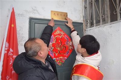 社区人员为辖区军人安装门牌